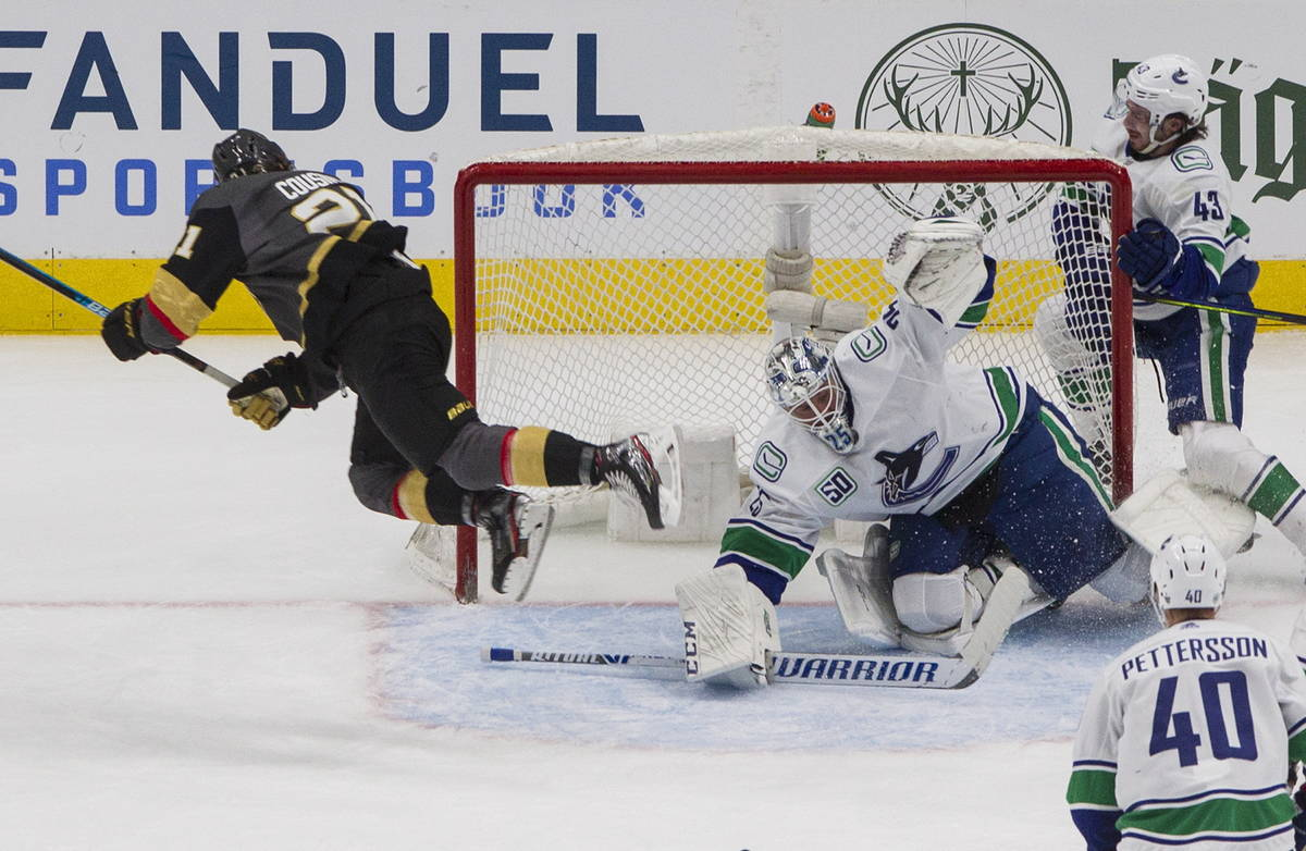 Vegas Golden Knights' Nick Cousins (21) jumps over Vancouver Canucks goalie Jacob Markstrom (25 ...