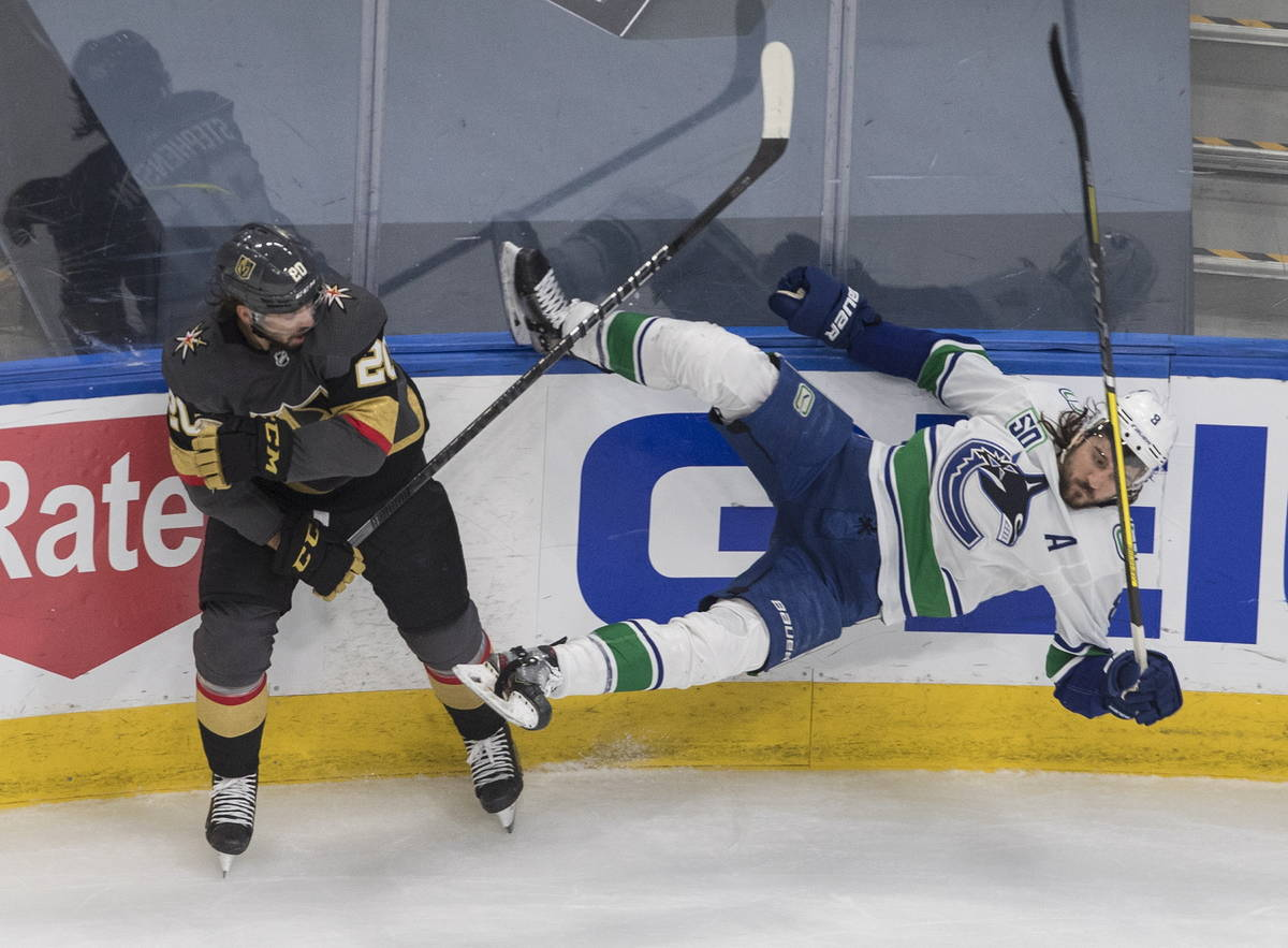 Vegas Golden Knights' Chandler Stephenson (20) checks Vancouver Canucks' Christopher Tanev (8) ...