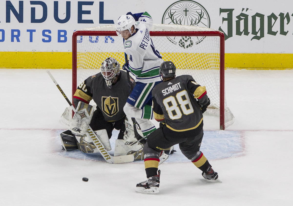 Vegas Golden Knights' goalie Robin Lehner (90) makes the save as Vancouver Canucks' Elias Pette ...