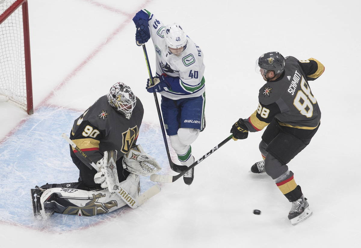 Vegas Golden Knights' goalie Robin Lehner (90) makes the save as Vancouver Canucks Elias Petter ...