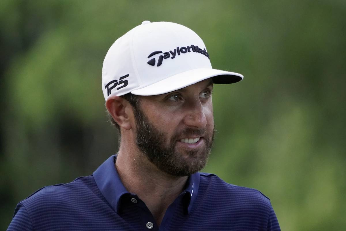 Dustin Johnson smiles as he walks to the 17th tee during the final round of the Northern Trust ...