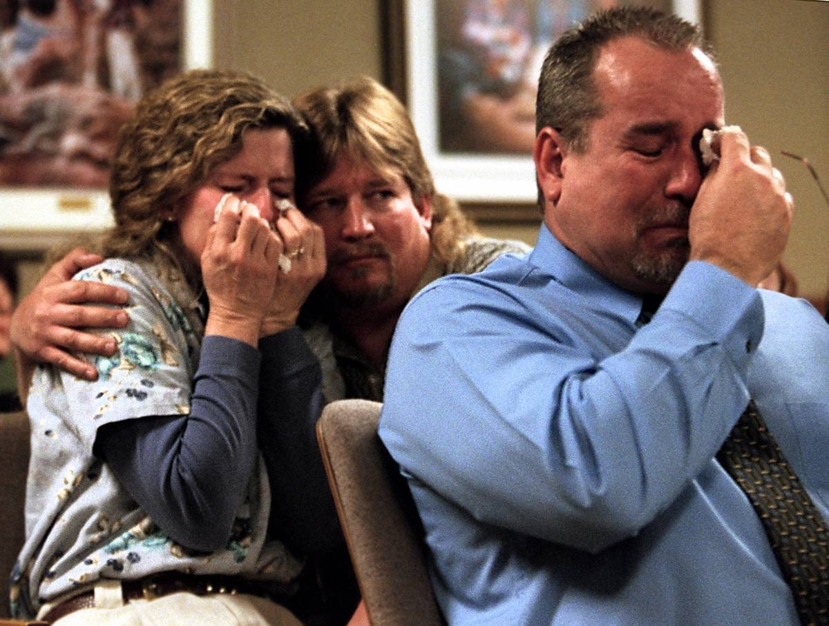 Doug Gould embraces his wife, Viola, and Dale Booth wipes his eyes while listening to Clark Cou ...