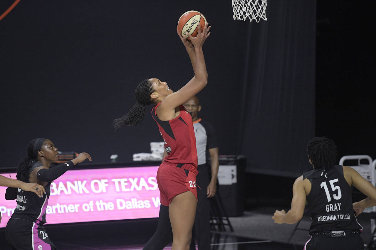 Las Vegas Aces center A'ja Wilson (22) goes up for a shot between Dallas Wings guards Arike Ogu ...