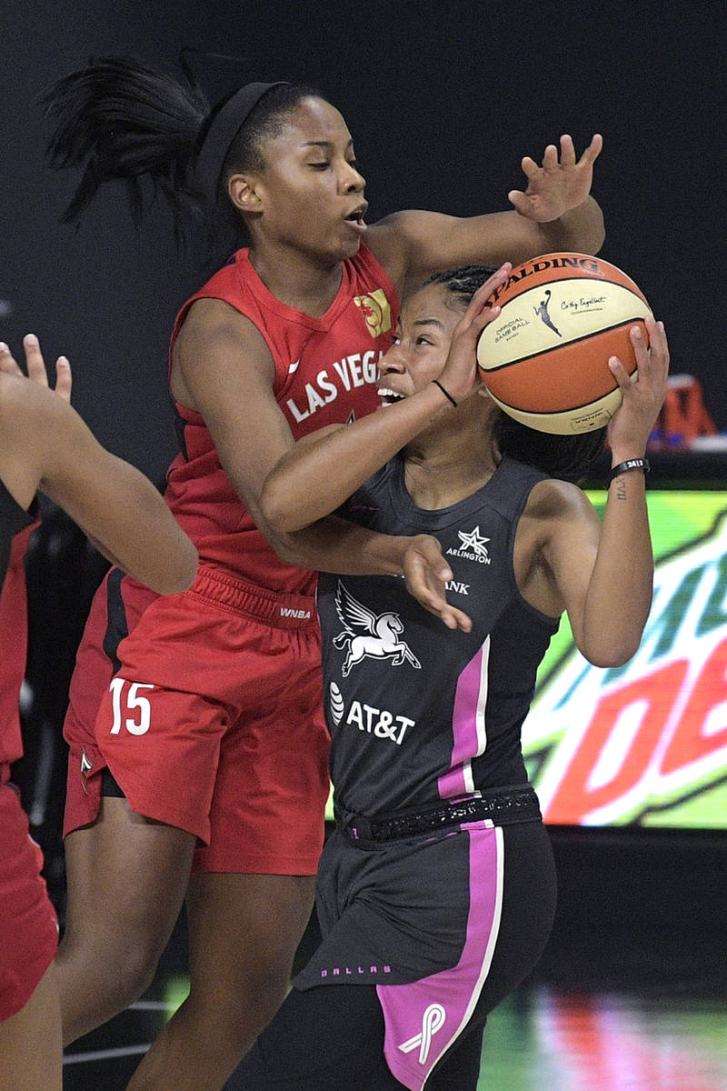 Dallas Wings guard Tyasha Harris, right, is fouled by Las Vegas Aces guard Lindsay Allen, left, ...