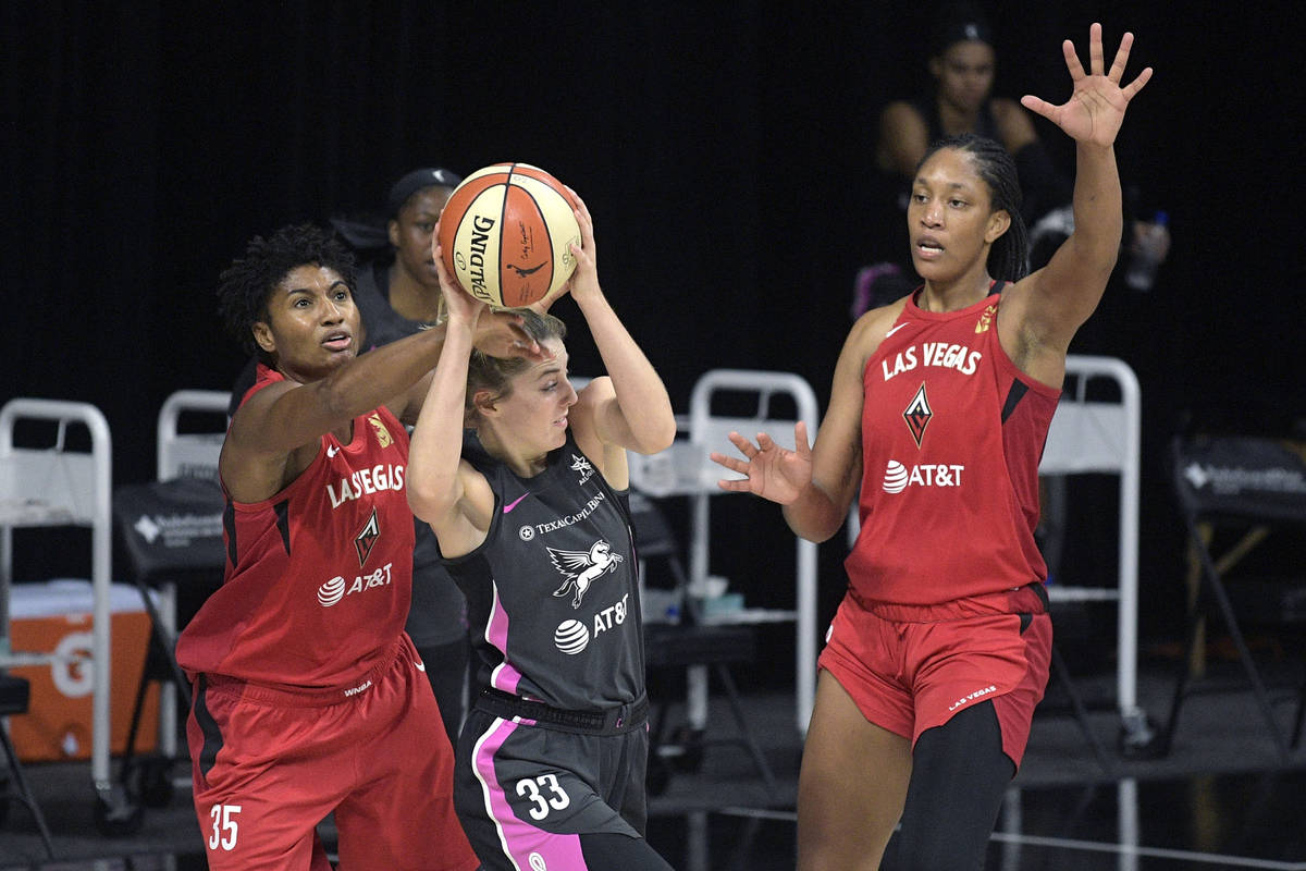 Dallas Wings guard Katie Lou Samuelson, center, is fouled by Las Vegas Aces forward Angel McCou ...