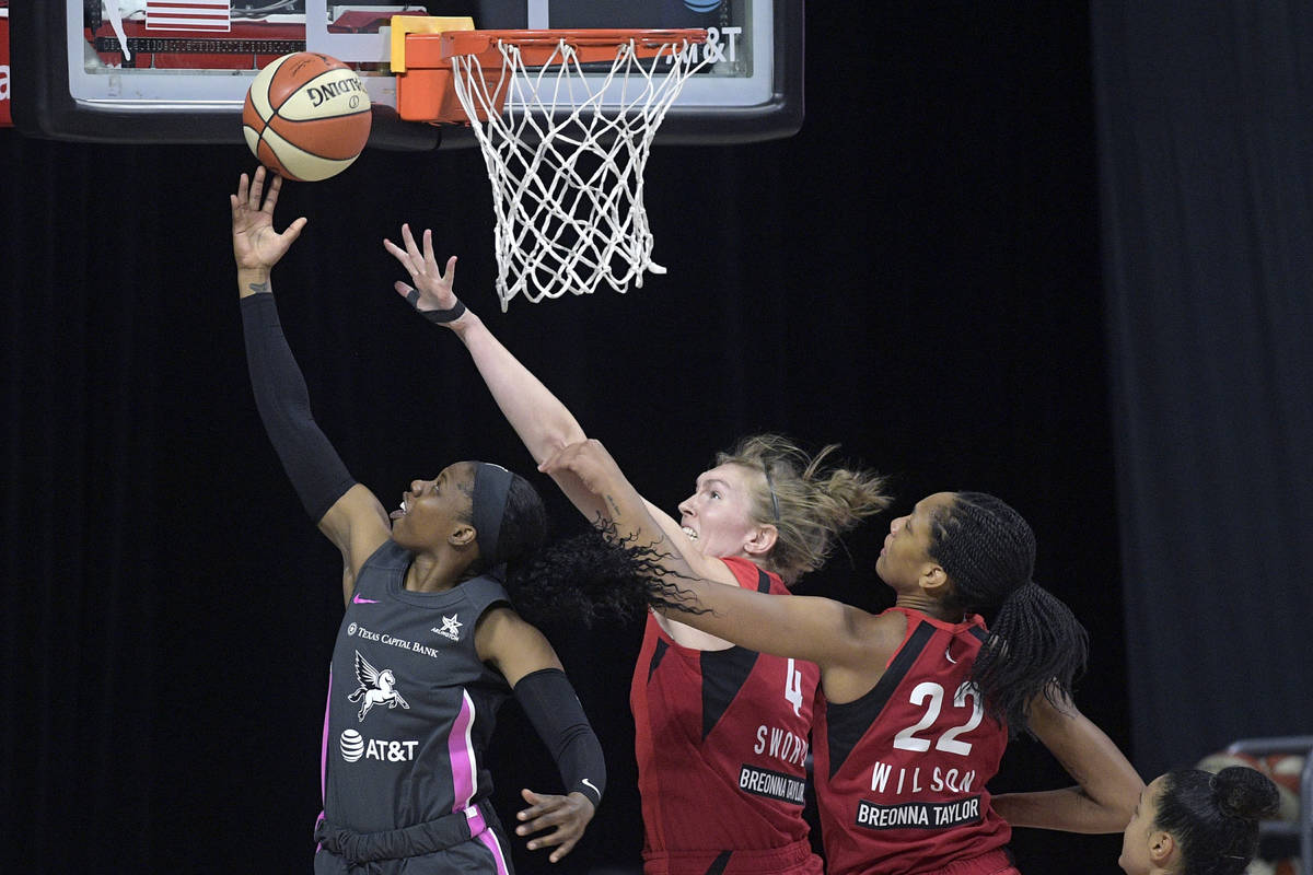 Dallas Wings guard Arike Ogunbowale (24) goes up for a shot in front of Las Vegas Aces center C ...