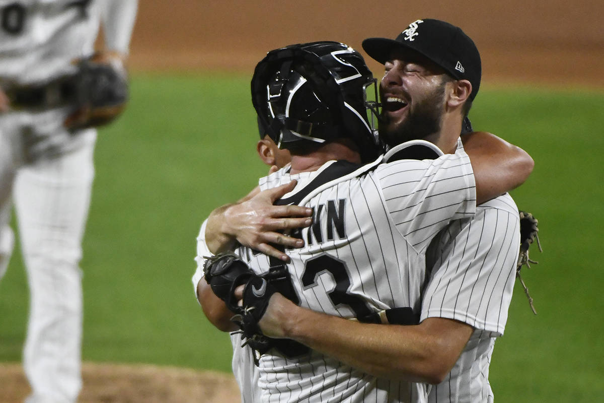 Chicago White Sox starting pitcher Lucas Giolito, right, hugs catcher James McCann and Jose Abr ...