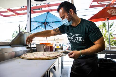 Mimmo Ferraro, owner and chef at Pizza Forte, right, prepares a pizza in the University Gateway ...