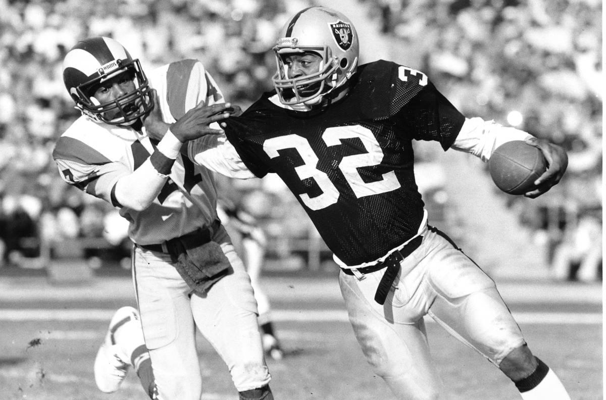 Los Angeles Raiders running back Marcus Allen (32) fends off Los Angeles Rams cornerback LeRoy ...