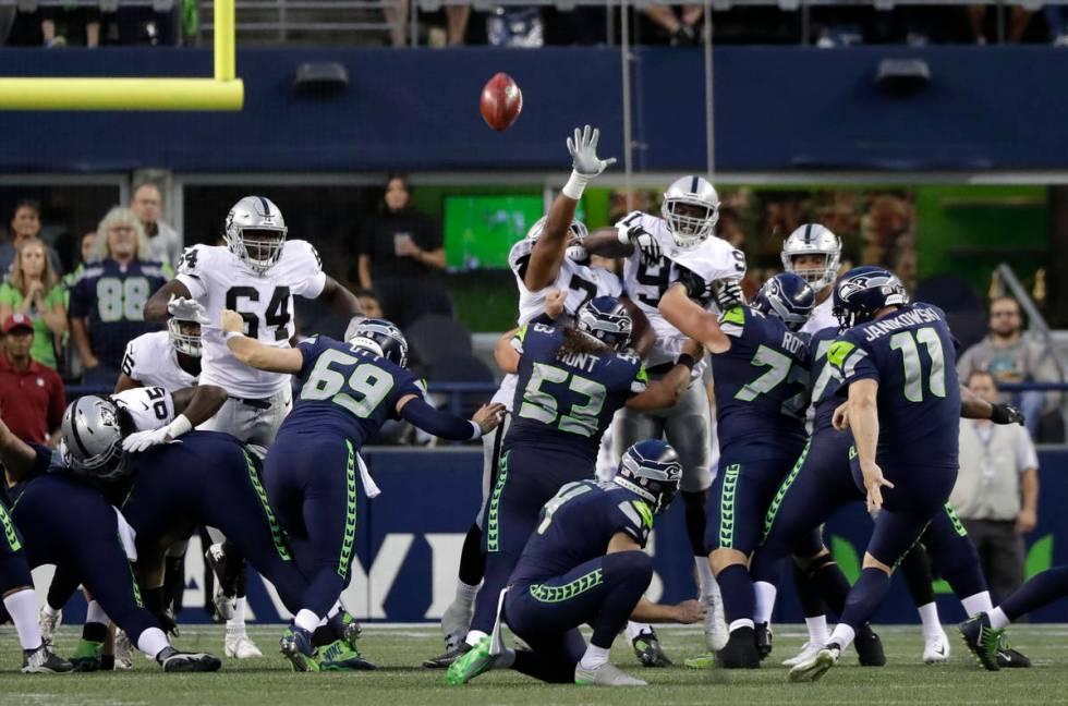 Seattle Seahawks kicker Sebastian Janikowski (11) kicks a point after following a touchdown aga ...