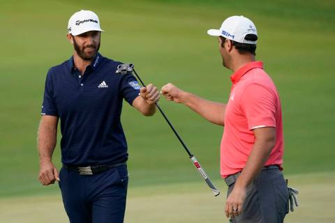 Jon Rahm, right, is congratulated by Dustin Johnson on the first playoff hole during the final ...