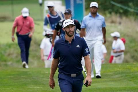 Dustin Johnson walks on the 13th fairway in front of Hideki Matsuyama, of Japan, top right, dur ...