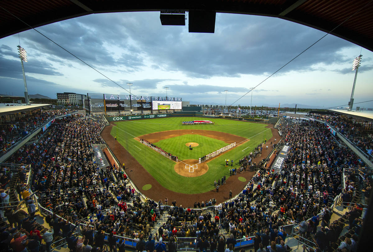 Four F-16 jets from Nellis Air Force Base fly over the ballpark with an American flag unfurled ...