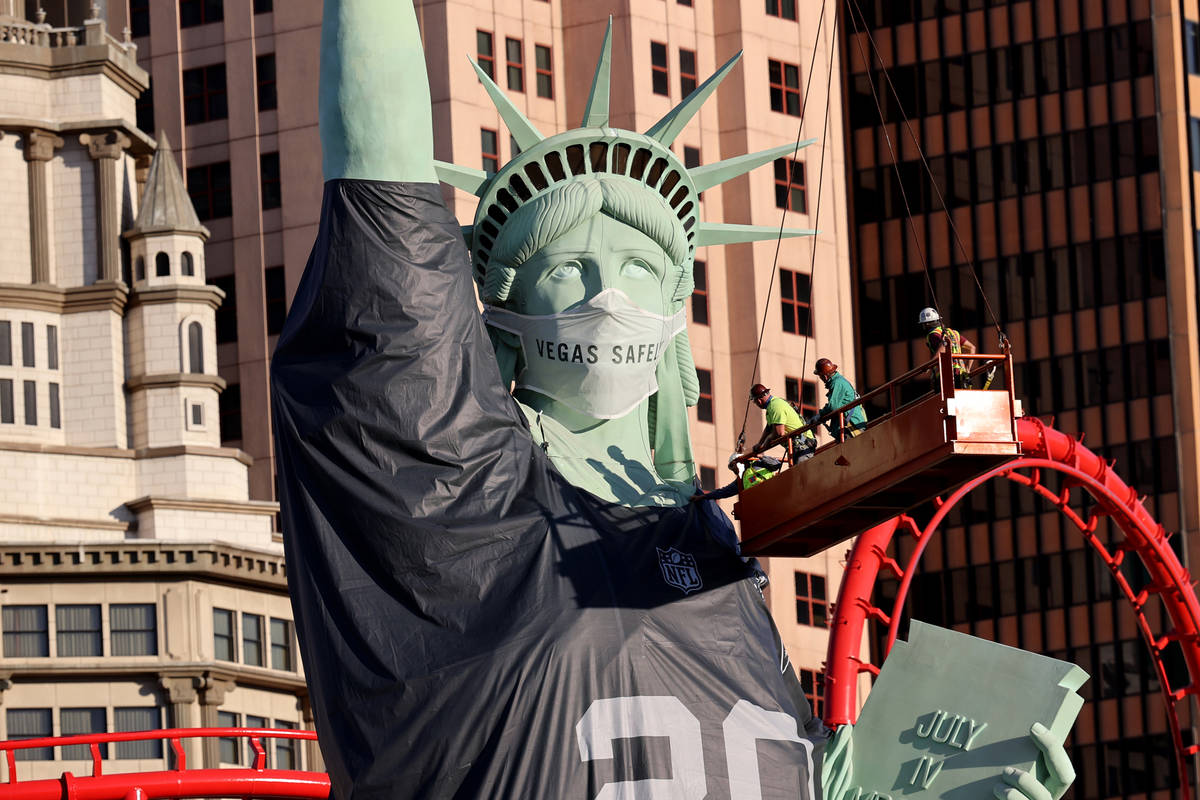Workers install a a Las Vegas Raiders jersey on the Statue of Liberty replica at New York-New Y ...