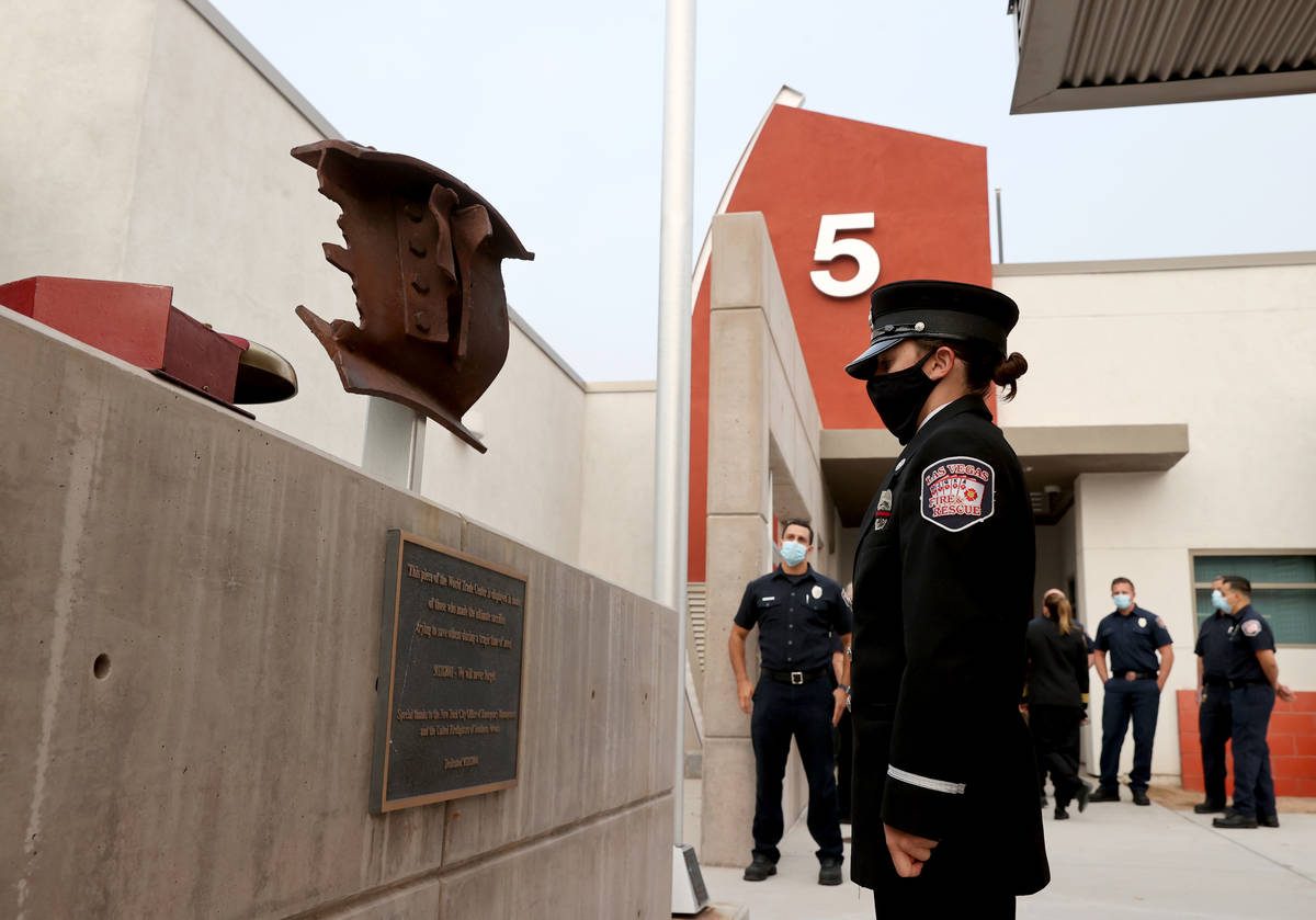 Las Vegas firefighter Lisa Leonard takes a moment with a piece of New York's World Trade Center ...