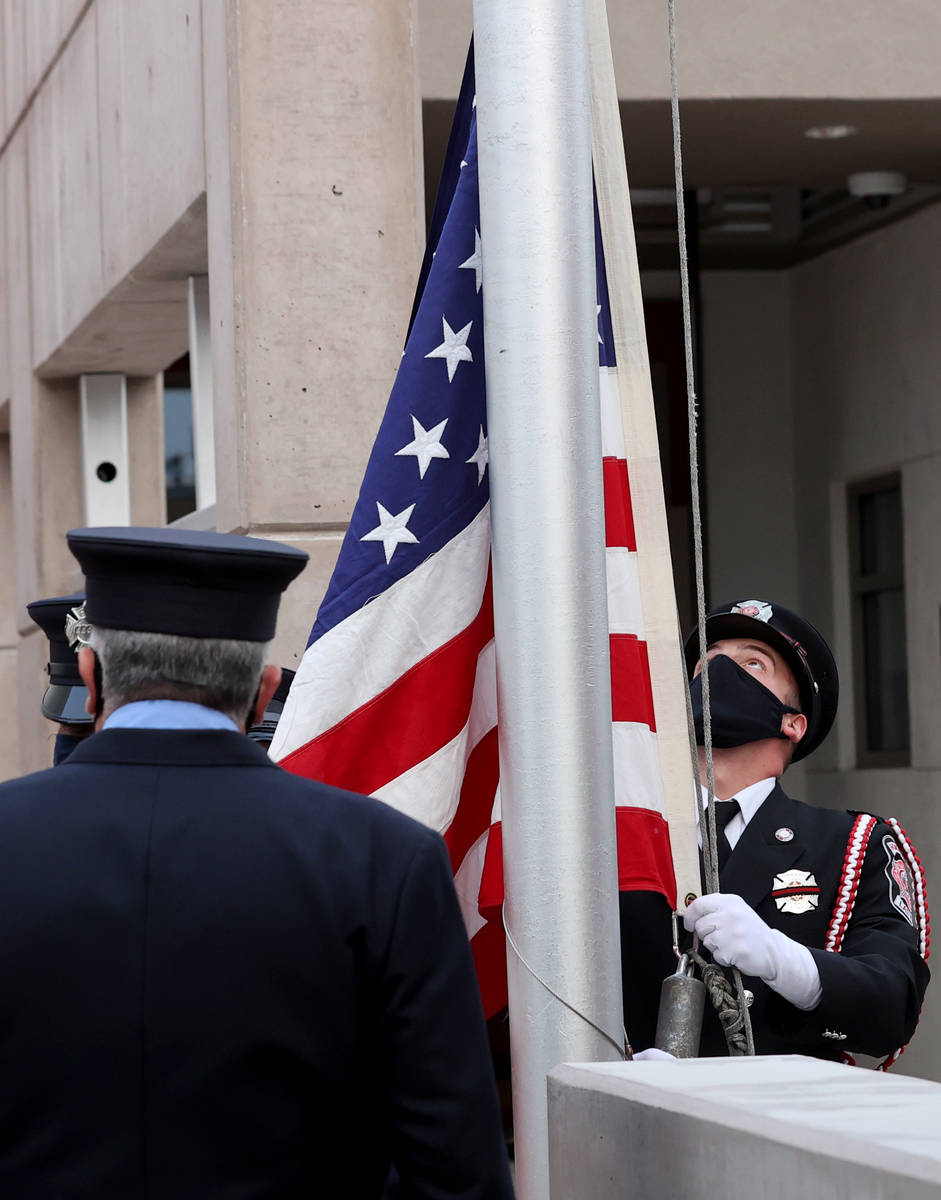 Las Vegas Fire engineer Brian Dietz prepares to raise a flag that flew at the World Trade Cente ...