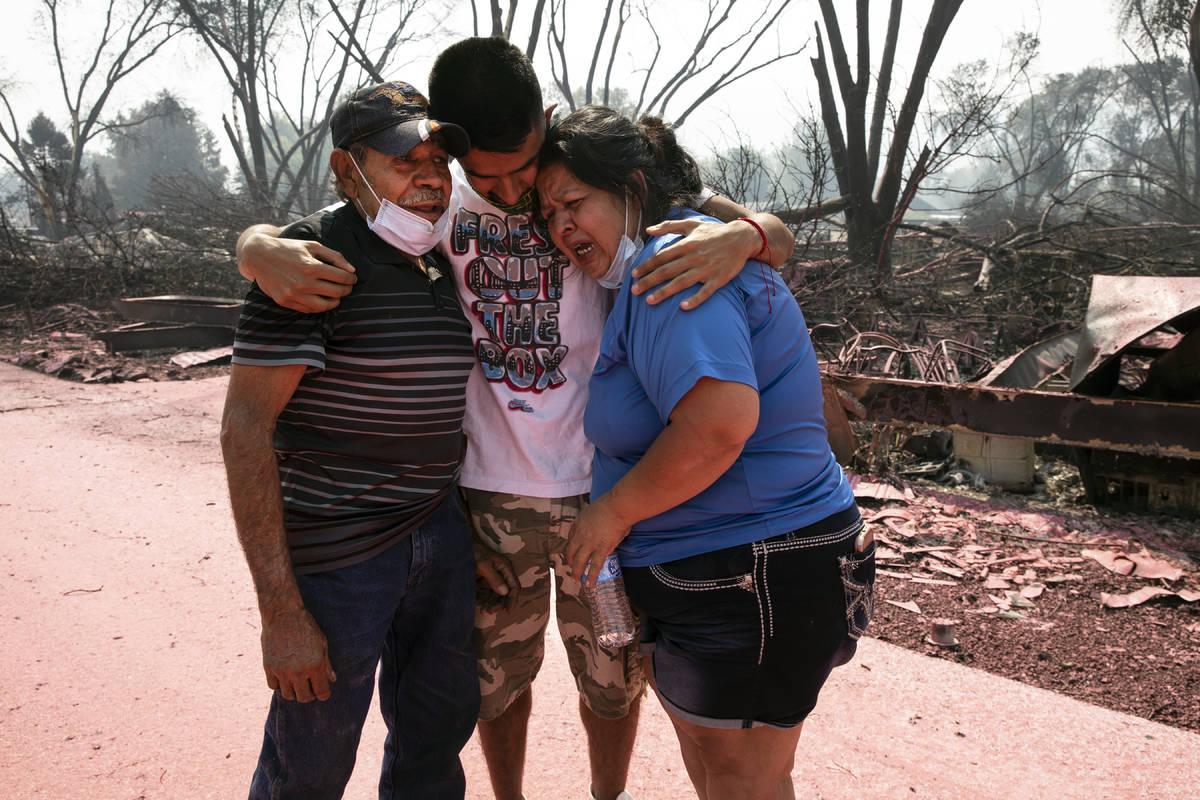 Dora Negrete, right, and her husband Marcelino Rocha, left, and son Hector Rocha console each o ...