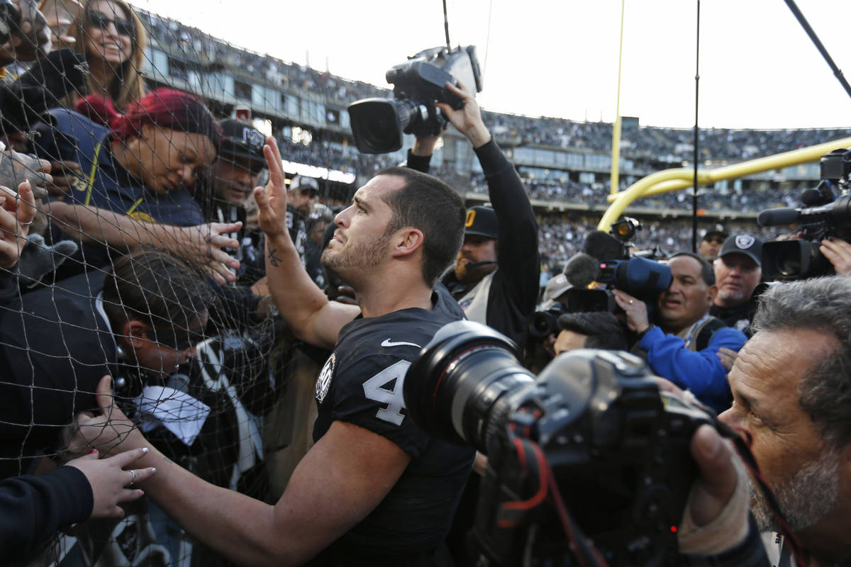 """Oakland Raiders quarterback Derek Carr is greeted by fans in """"The Black Hole"""" after a ..."""