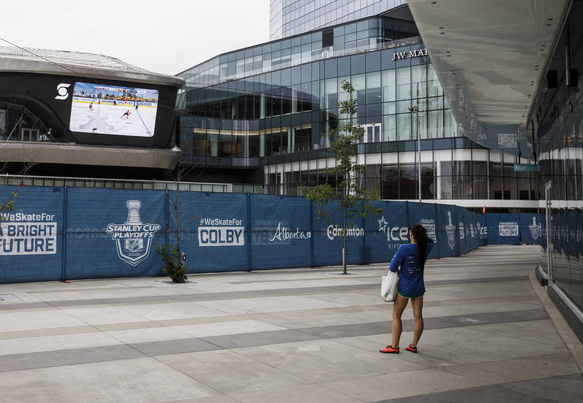 FILE - A woman watches a hockey game on the big screen just outside the bubble at the NHL Weste ...