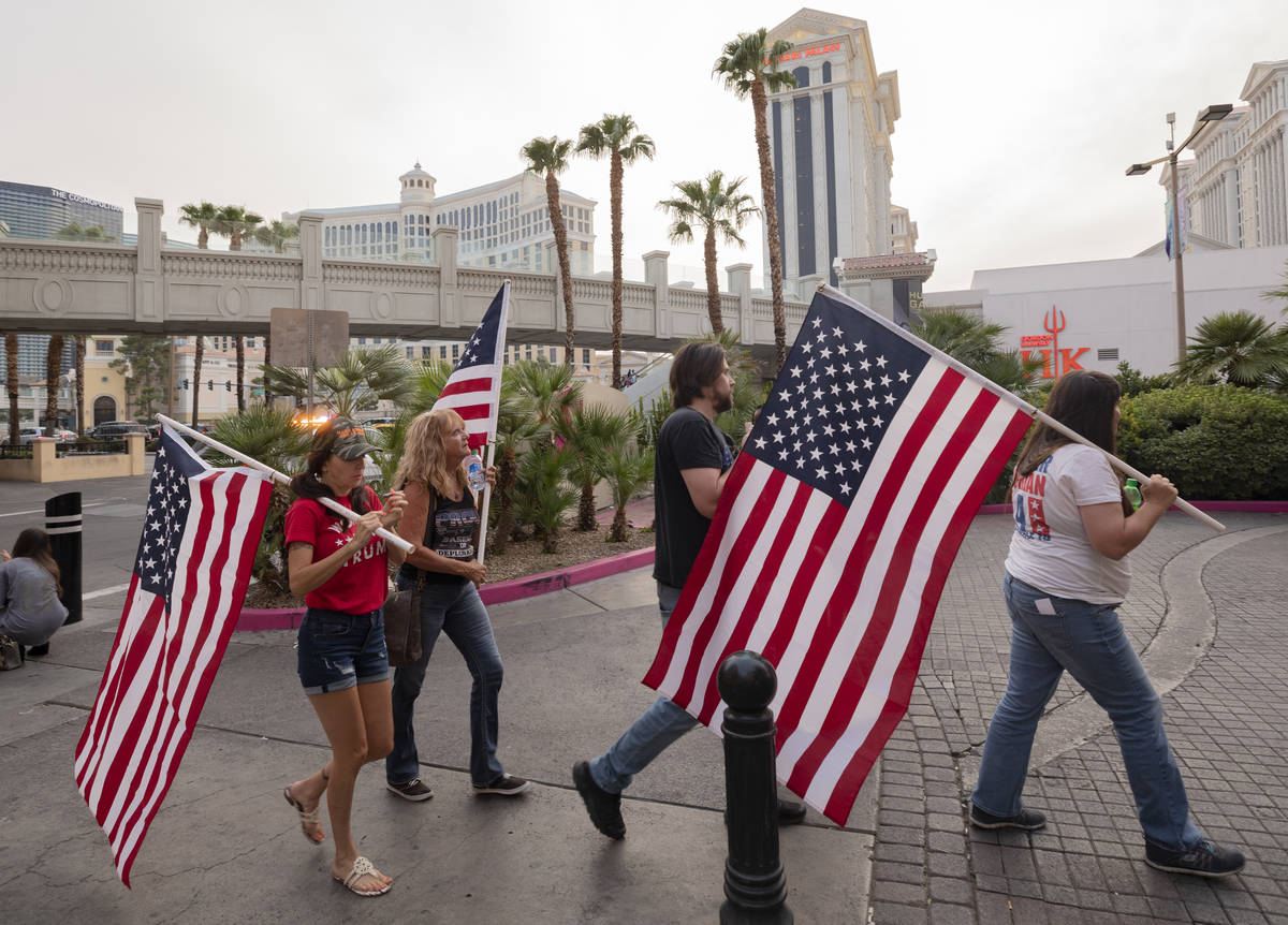 Individuals walk down the Las Vegas Strip rallying for Make Nevada Red, and Fight for Nevada, o ...