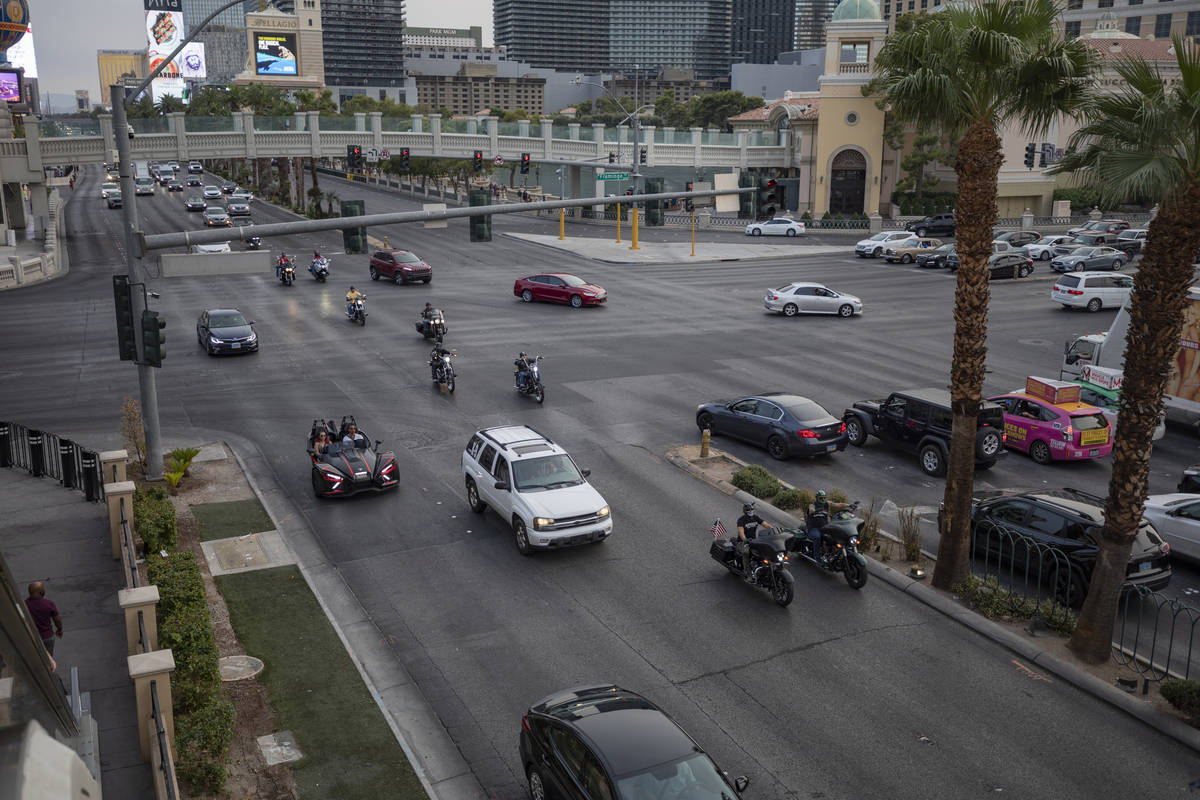 A caravan of motorcycles with American flags are seen driving down the Las Vegas Strip on Frida ...