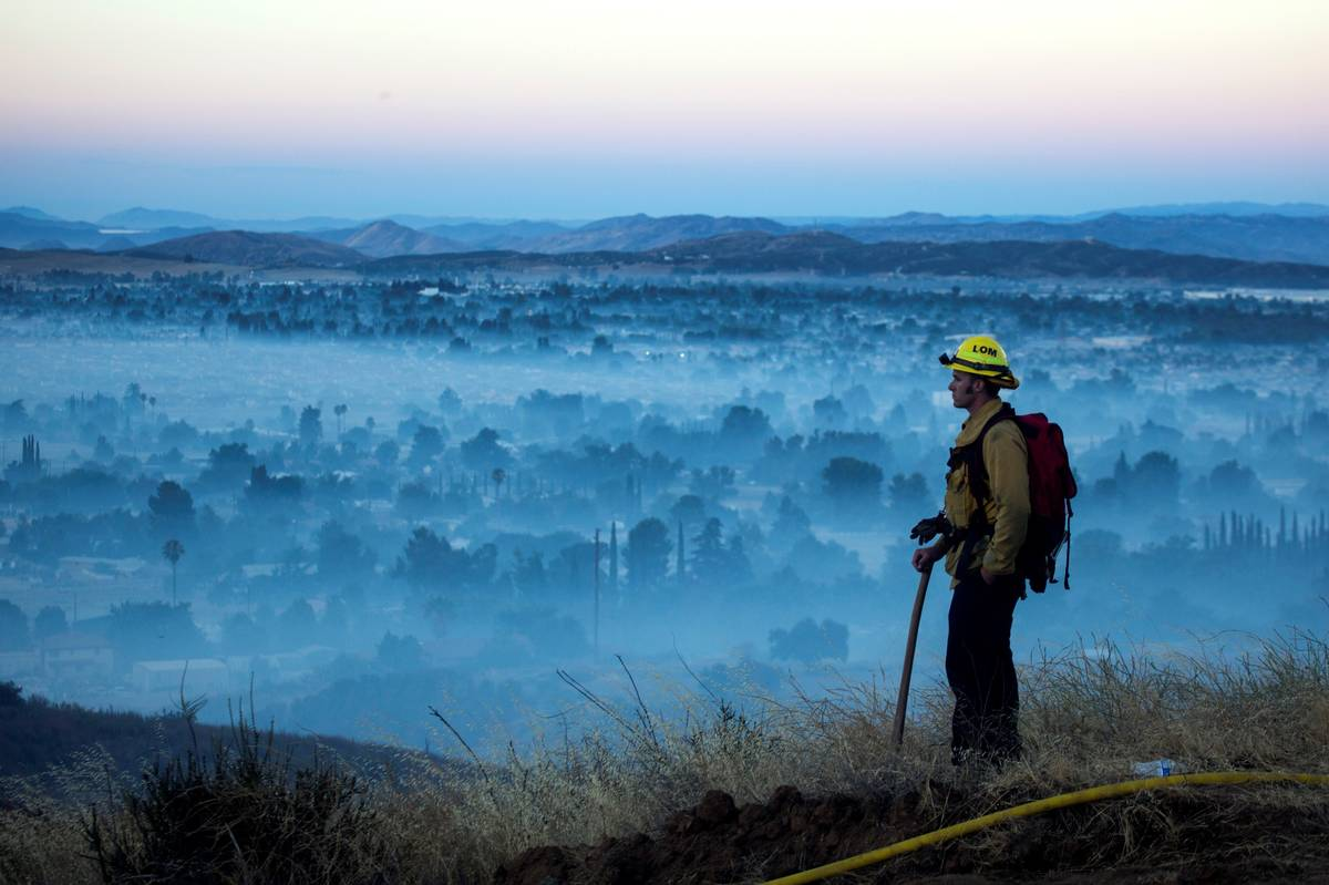 A firefighter watches during the Apple Fire in Cherry Valley, Calif., in August 2020. (AP Photo ...