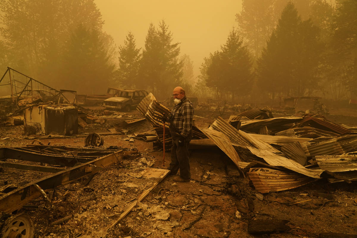 George Coble walks through what remains of a home on his property destroyed by a wildfire Satur ...