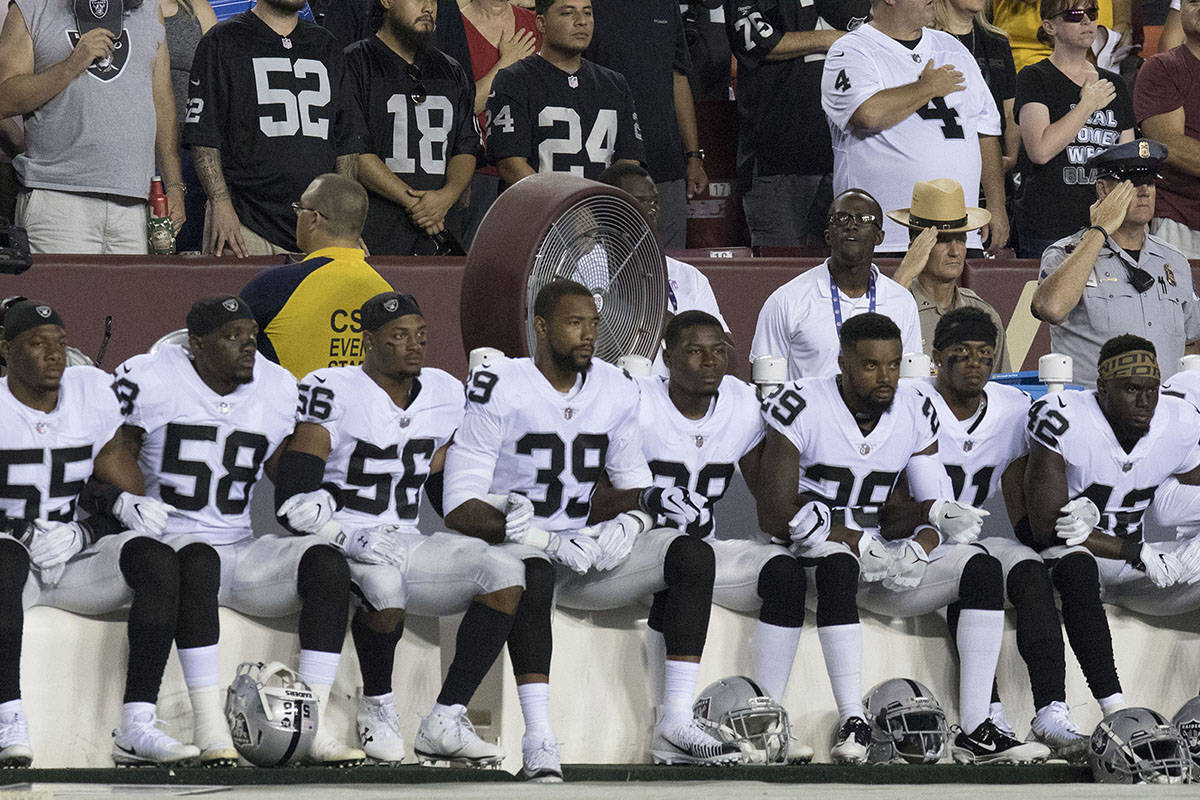 Some of the Oakland Raiders interlock arms and sit during the national anthem before their game ...