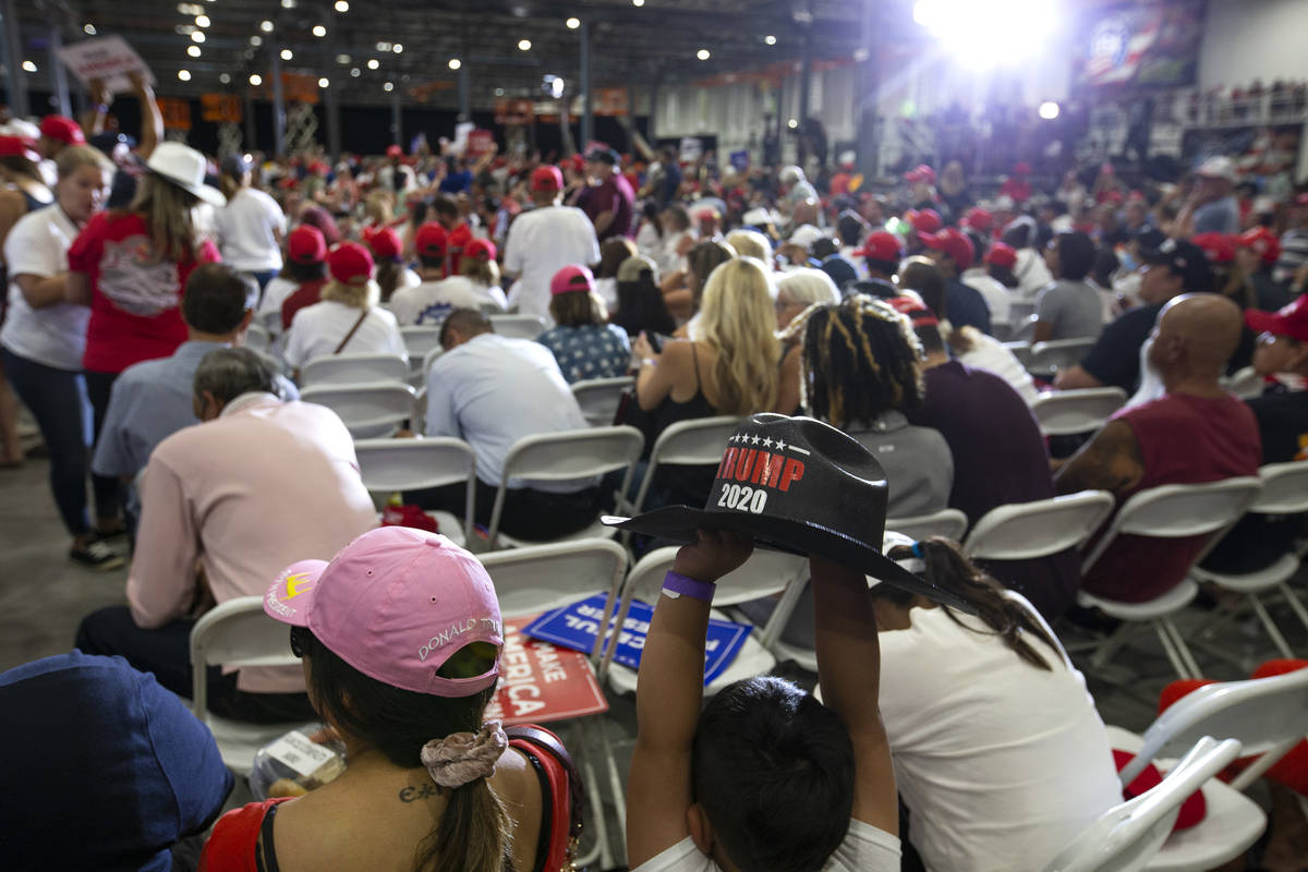 A young Trump campaign rally attendee holds up a Trump-branded cowboy hat at Xtreme Manufacturi ...