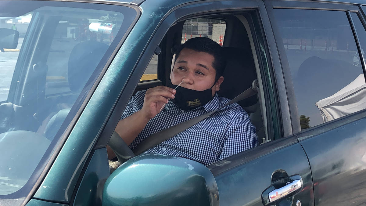 "Vincent Nava swabs his nose during his COVID-19 test at the ""Stop, Swab & Go!"" drive-thru testi ..."