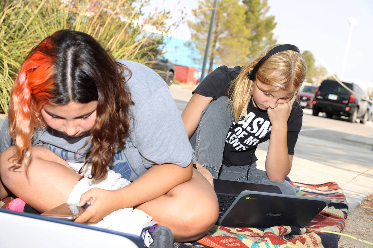 Imogen Dedmon, 15, left, and her sister Shayne, 13, participate in their virtual classes using ...