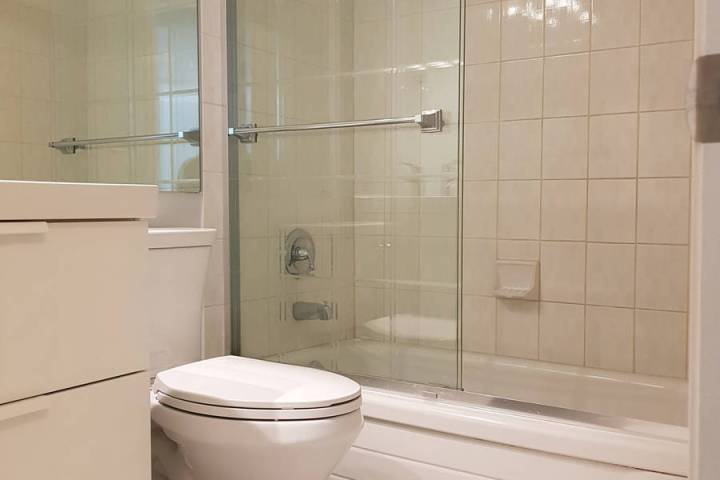 Most doors on tub enclosures hang from the top rail and slide along its guide track. (Getty Images)
