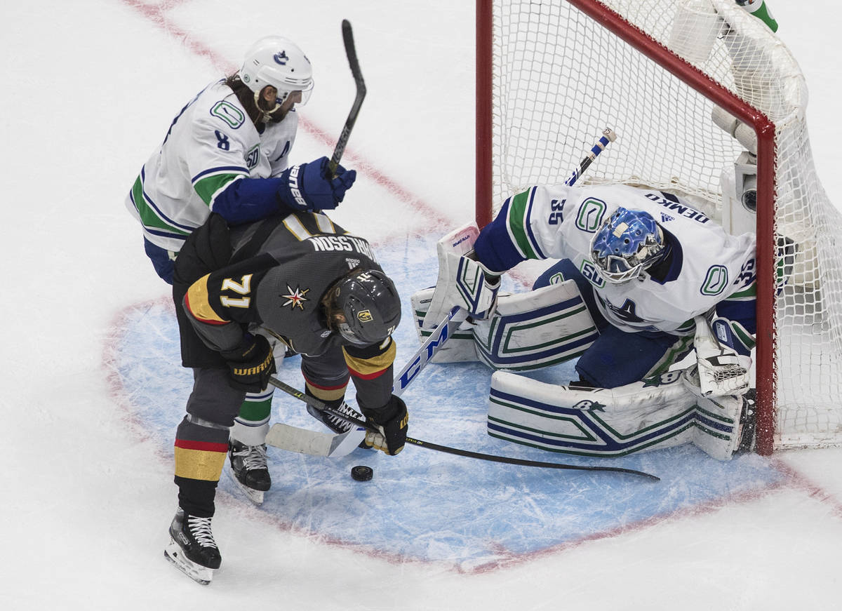 Vancouver Canucks goalie Thatcher Demko (35) makes a save on Vegas Golden Knights' William Karl ...