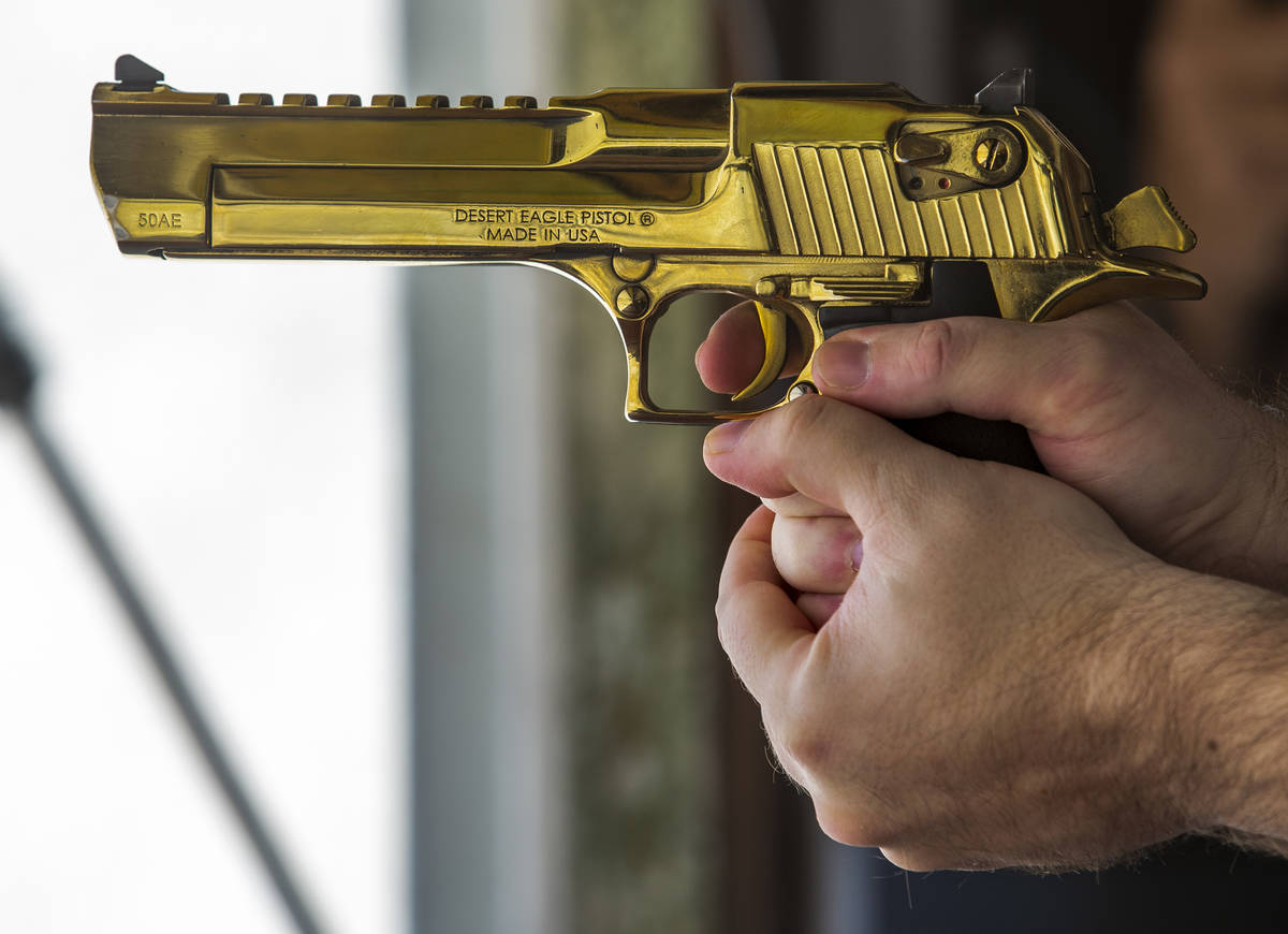 Adrenaline Mountain owner and CEO Eric Brashear readies to fire a titanium gold Desert Eagle pi ...