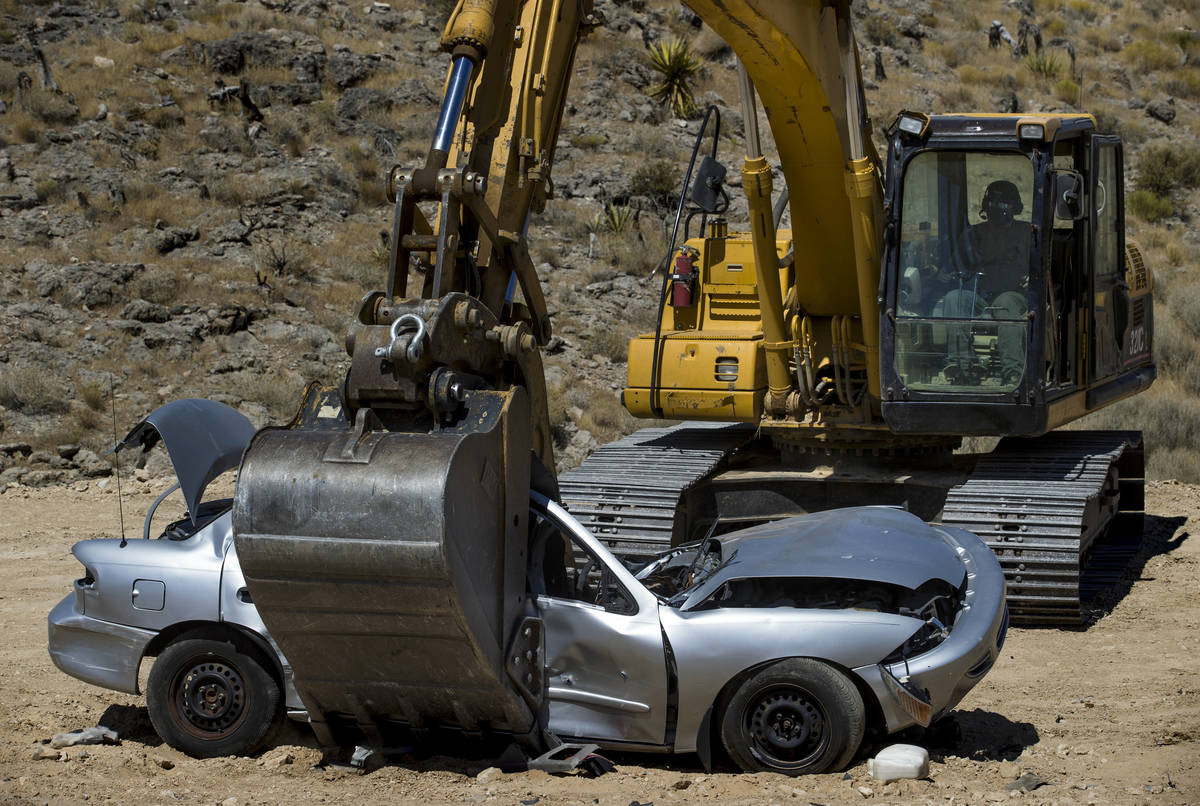 Christopher Lawrence crushes a car with the use of a Caterpillar Excavator, one of the extreme ...
