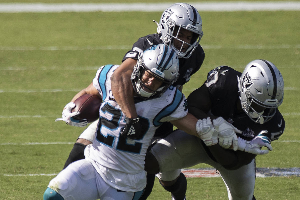 Carolina Panthers running back Christian McCaffrey (22) is tackled by Las Vegas Raiders safety ...