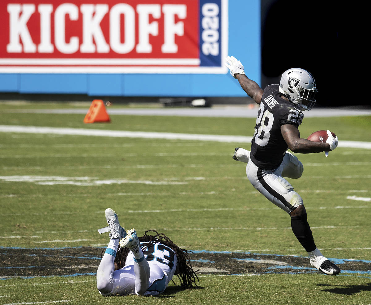 Las Vegas Raiders running back Josh Jacobs (28) leaps over Carolina Panthers safety Tre Boston ...