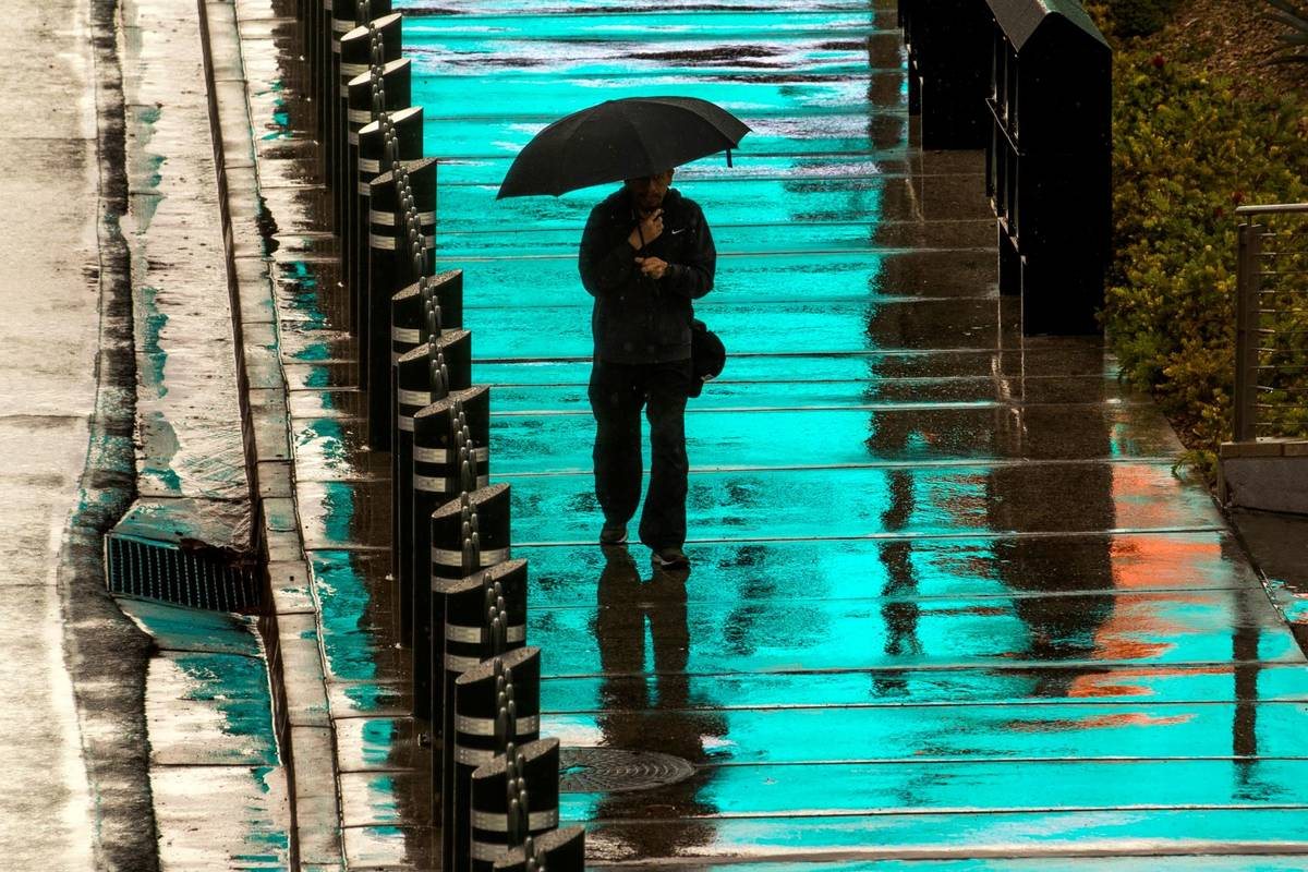 A pedestrian is bathed in blue light from a lighted sign above as he walks in the rain about th ...