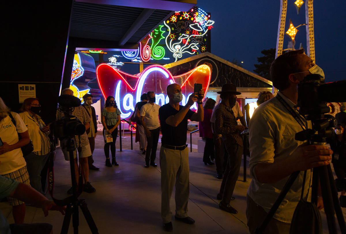 People take pictures before the reillumination of the Moulin Rouge sign at the Neon Museum in L ...