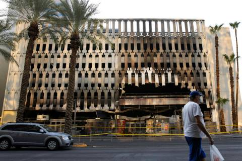 A pedestrian walks past the 4 Queens hotel-casino parking garage where at least five vehicles c ...