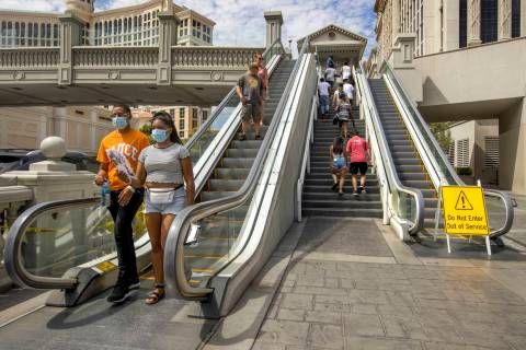 Pedestrians work their way down and up the bridge that crosses East Flamingo Road between Caesa ...