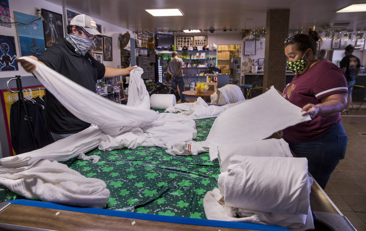 Connie West, right, and her son Cody Theising, fold bedding for their rooms at the Little A'Le' ...