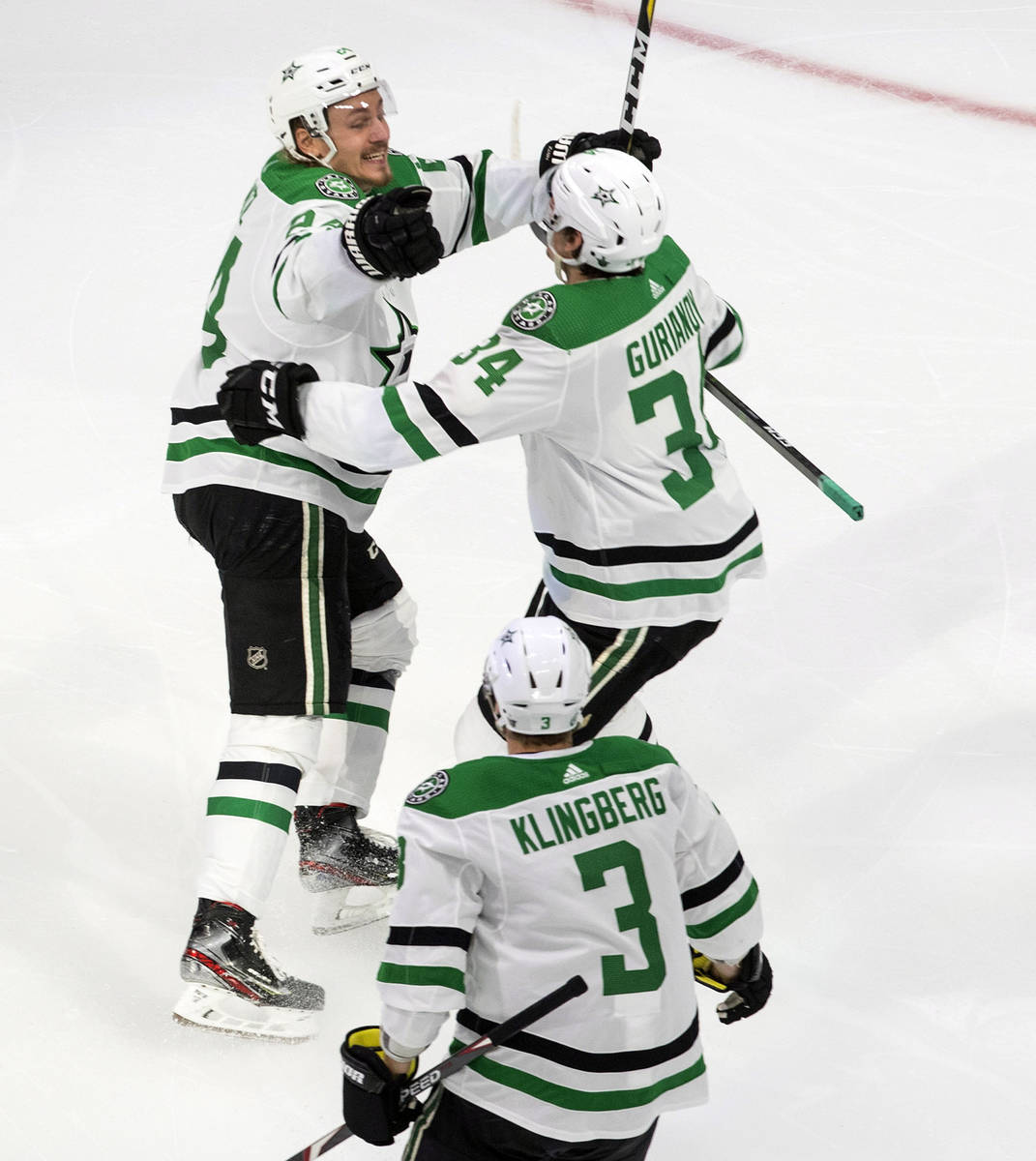 Dallas Stars' Denis Gurianov (34), Roope Hintz (24) and John Klingberg (3) celebrate their win ...
