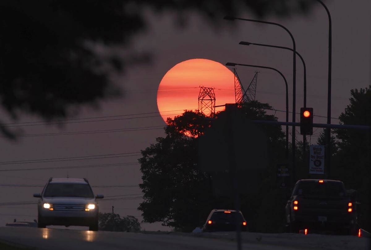 Traffic flows on Townline Road as a hazy sun sets in Vernon Hills, Ill,, Tuesday, Sept. 15, 202 ...