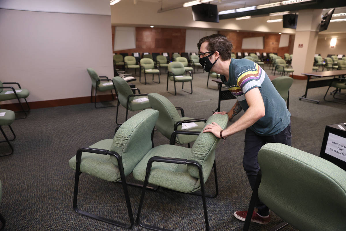 Jury Clerk Salvatore Savini removes extra chairs from the updated Regional Justice Center jury ...