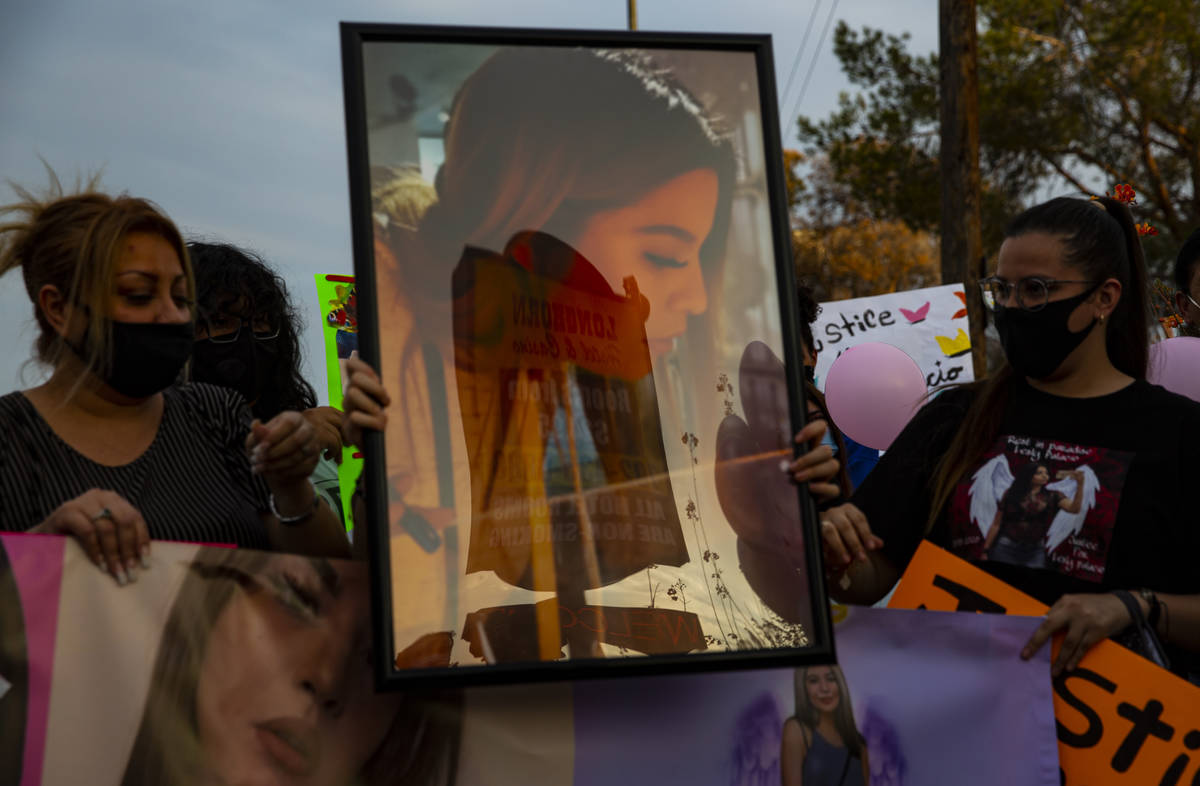 Family members and other people hold pictures of Lesly Palacio, who was found slain near Valley ...