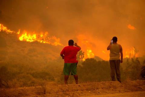 People take photos as the Bobcat Fire burns in Juniper Hill, Calif., Friday, Sept. 18, 2020. (A ...