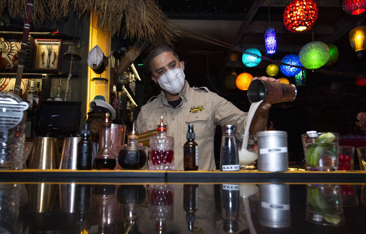 Bartender Jason Reyes poors a tiki cocktail on the first night that bars reopened since coronav ...