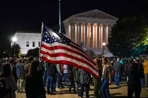 People gather at the Supreme Court in Washington, Saturday night, Sept. 19, 2020, to honor the ...
