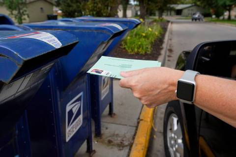 A person drops applications for mail-in ballots into a mailbox in Omaha, Neb., Aug. 18, 2020. ...